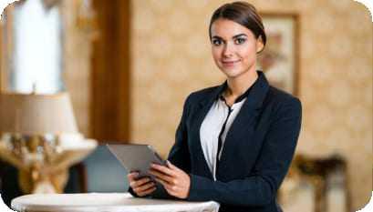 Jovem profissional da área de hotelaria e recepção segurando um tablet.