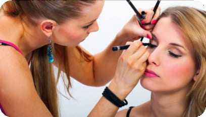 Profissional especializada fazendo uma maquiagem numa cliente.