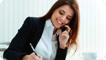 Jovem moça atuando como assistente administrativo e atendendo clientes pelo telefone.