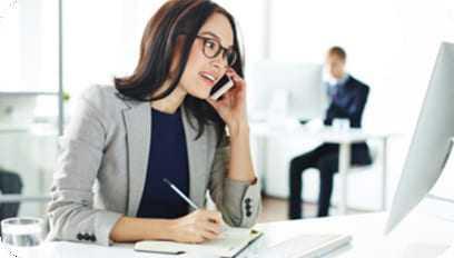 Moça trabalhando como secretária atendendo cliente pelo telefone.