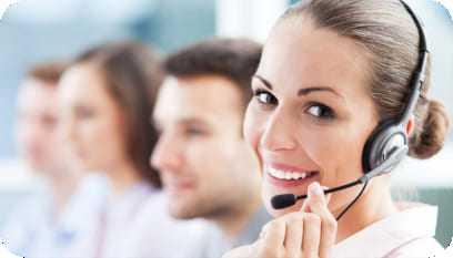 Operadora de telemarketing sorrindo enquanto segura seu headset